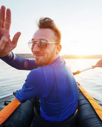 man floating on lake in a kayak at fantastic sunset.